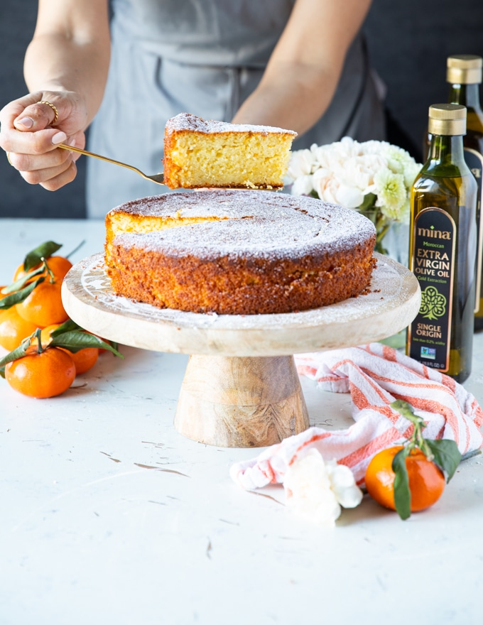A hand holding a slice of olive oil cake over the serving olate with some clementine oranges and a tea towel around it