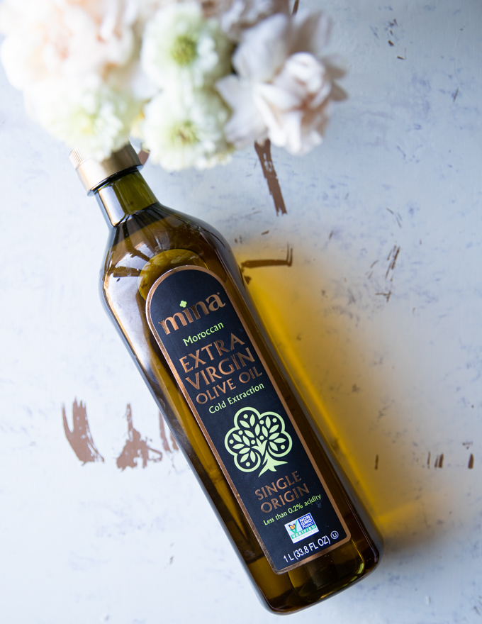 One bottle of moroccan olive oil surrounded by flowers