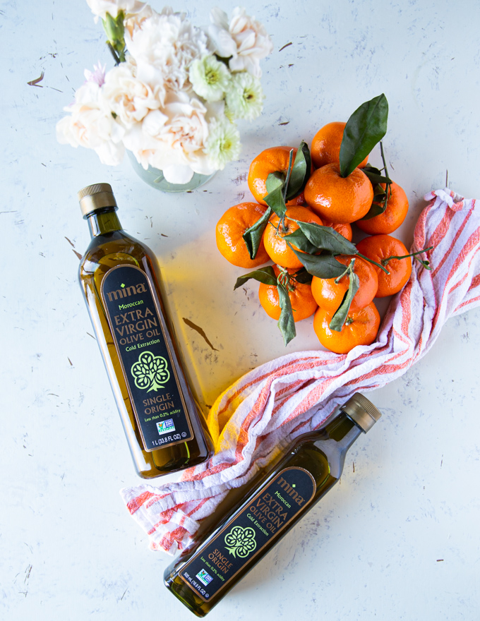 two bottles of Moroccan olive oil surrounded by clementine oranges and a tea towel