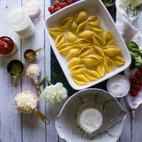 Ingredients for ricotta stuffed shells including pasta, ricotta, parmesan, mozzarella, spices, tomatoes, salt.