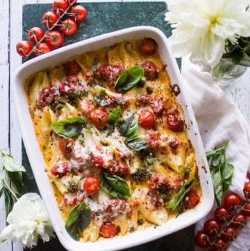 finished ricotta stuffed shells dish in a white baking dish on a table with tomatoes and flowers.