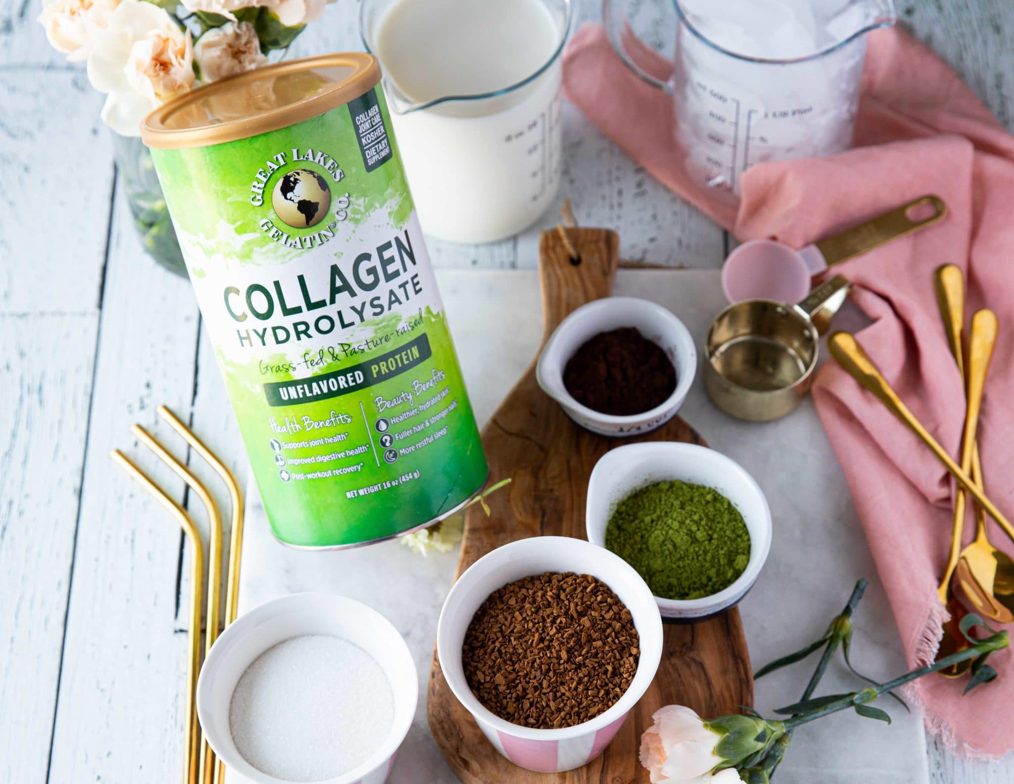 Ingredients for the whipped coffee recipe, the instant coffee in a cup, the sugar in a cp, the hot water, the cold milk, the ice, the matcha powder, the cocoa powder, collagen powder in a cup