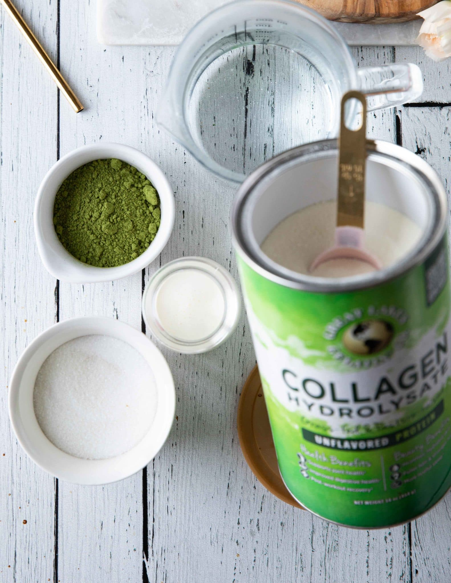 Ingredients for matcha dalgona with matcha powder, sugar, cream, collagen and an electric mixer