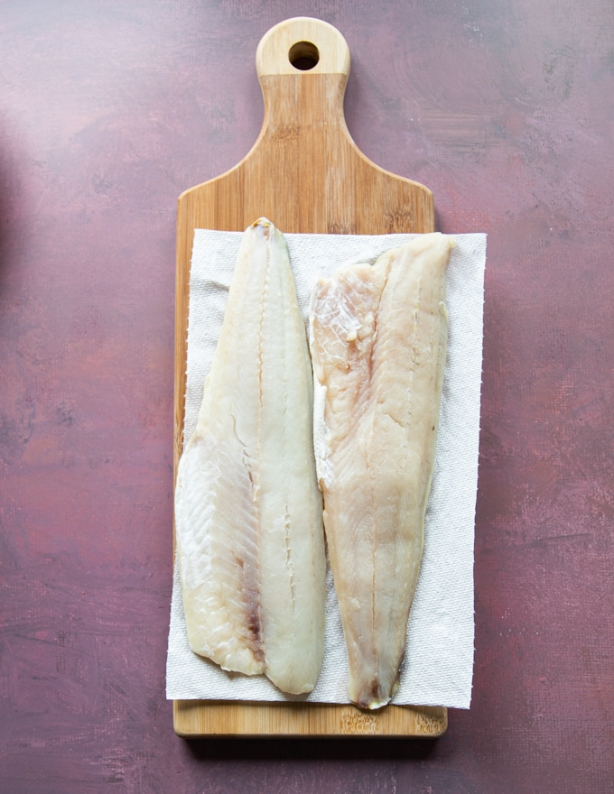 pickerel fillets on a cutting board thawing.