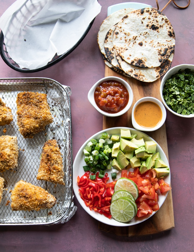ingredients for air fryer fish and to make air fryer fish tacos including tortillas charred, the ready fish, some chopped avocados, chipotle sauce, salsa, fresh cilantro and lime