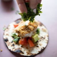 a flour tortilla with toppings like avocados, tomatoes, cilantro and then the air fryer fish is placed ontop and a hand is sprinkling more cilantro over the top