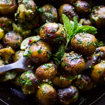 A spoon holding a few pan fried potatoes showing the crisp and herbs