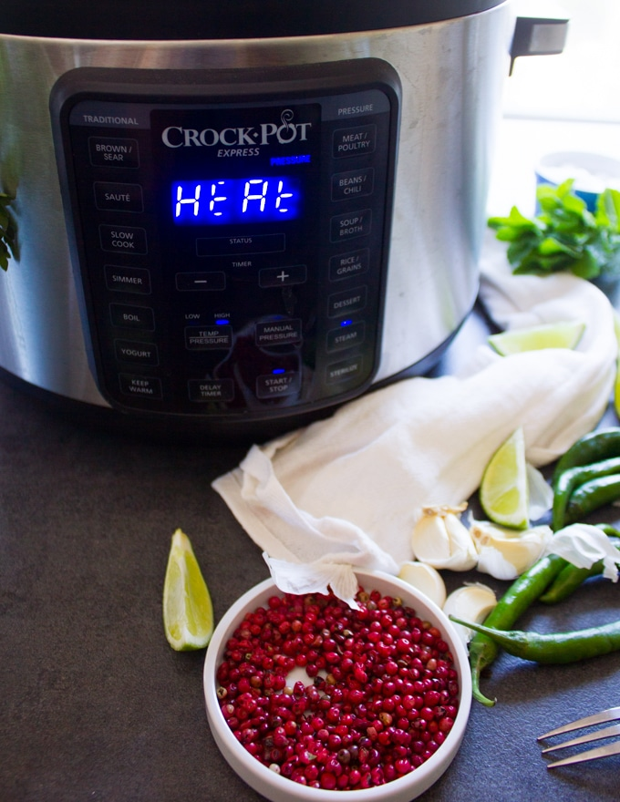 An instant pot or crock-pot turned on to cook the potatoes faster