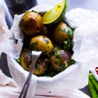 Pan fried potatoes served in a small bucket with a lime wedge