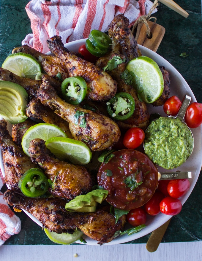 A full plate of air fryer chicken legs served with tomatoes, avocados, lime slices, guacamole and salsa