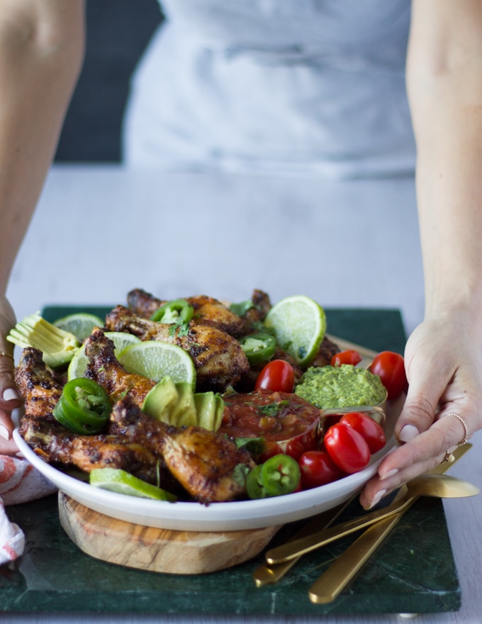 hand holding a plate of air fryer chicken recipe with tomatoes, avocados, lime wedges on a wooden board