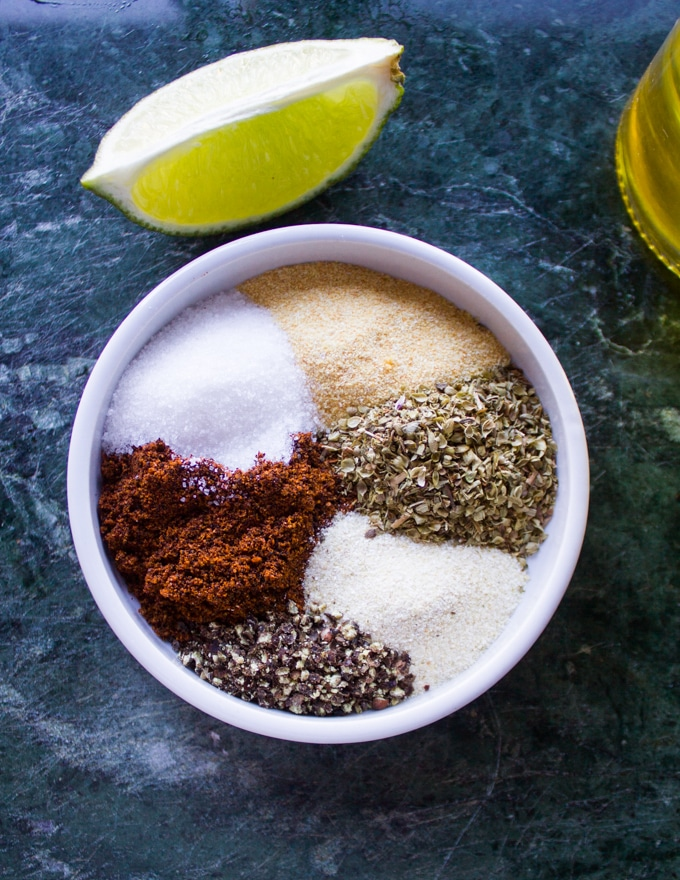a mall plate with al the spices needed for the chicken including, garlic powder, onion powder, chilli powder, salt, pepper and oregano
