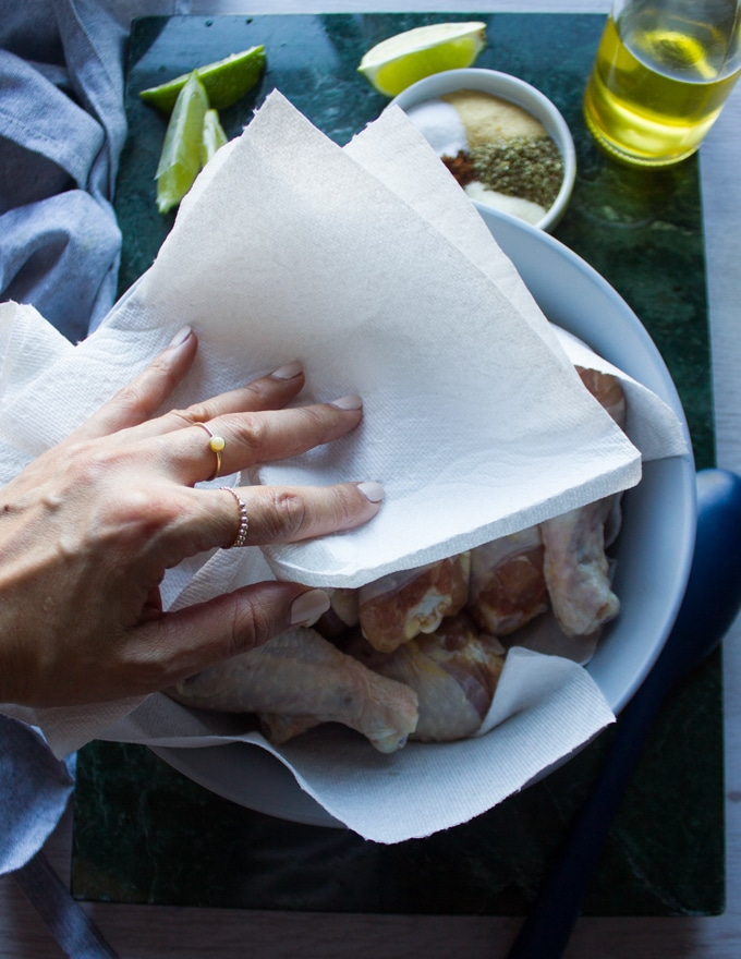 A hand patting the chicken legs dry using kitchen towels