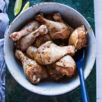 chicken legs coated with the dry spice mix in a bowl