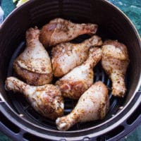 chicken legs coated with the spice mix and placed in an air fryer basket ready to air fry