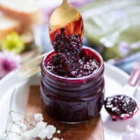 A spoon dripping from a blackberry jam jar showing the color and texture of the jam