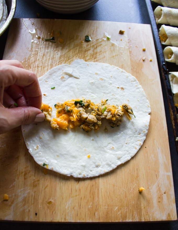 Chicken and cheese filling being placed in the center of the tortilla and ready to be rolled out into flautas