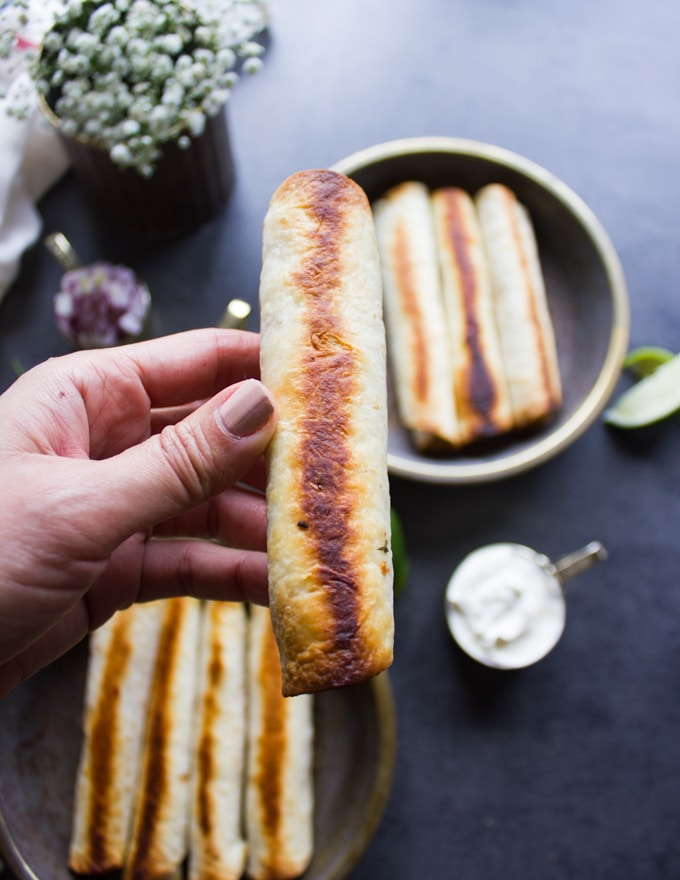 A hand holding a golden crisp chicken flautas out of the oven showing how crisp and golden it is