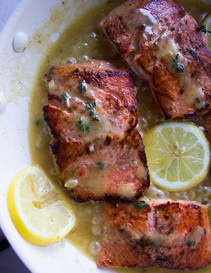 sockeye salmon recipe in a pan with lemon butter sauce and lemon slices cooked