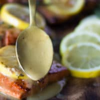 sockeye salmon on a plate and a hand drizzling the lemon butter sauce over the cooked sockeye salmon recipe