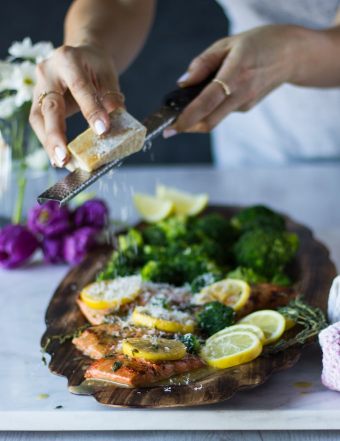 A hand grating some parmesan cheese over the top of the sockeye salmon recipe plated on a plate served with broccoli