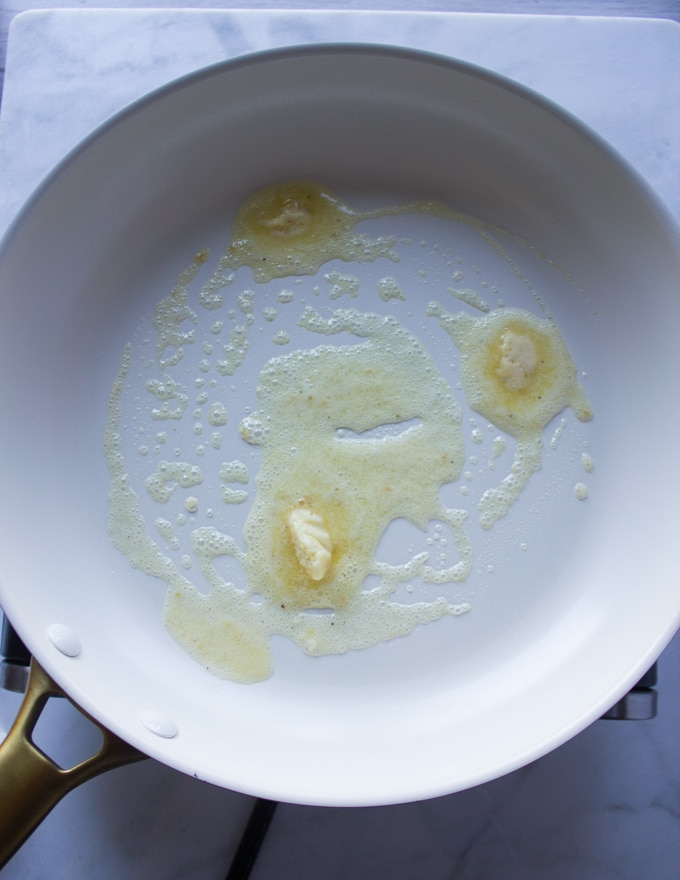 a sauce pan with butter preheating