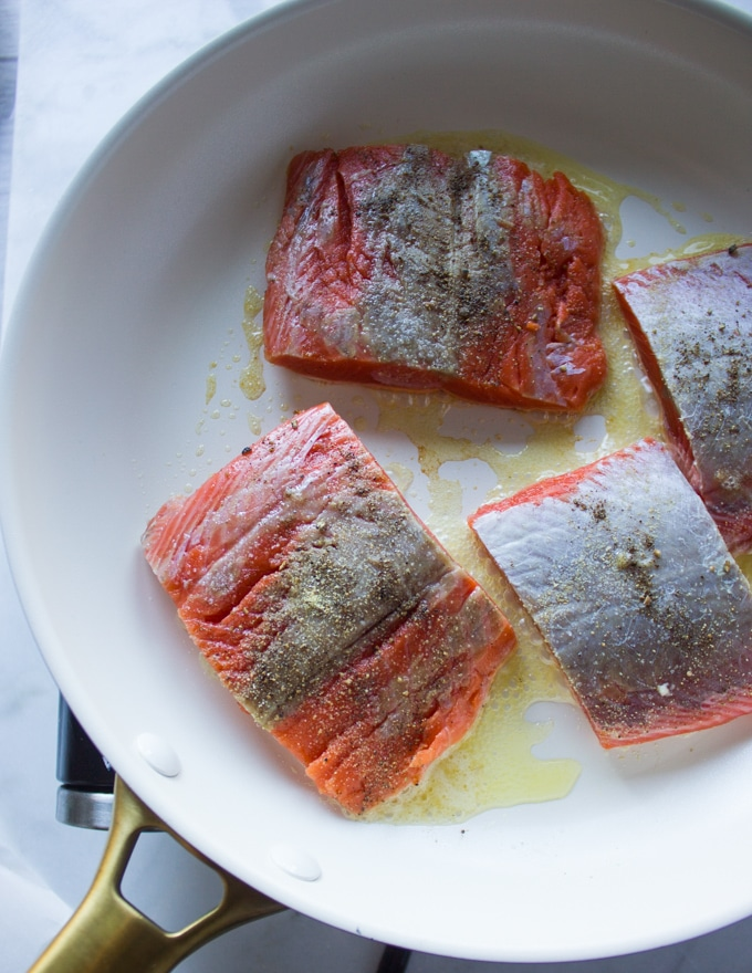 Sockeye salmon seasoned and placed in the buttered skillet to sear