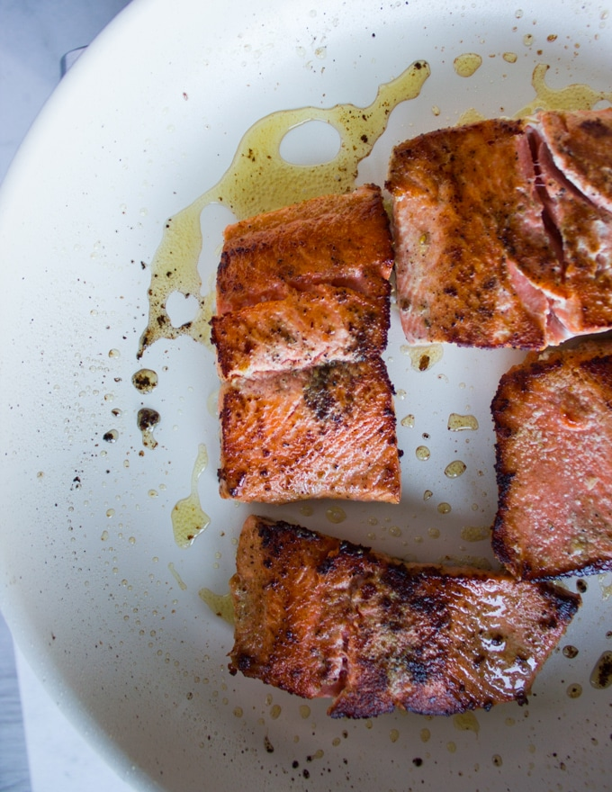 seared sockeye salmon golden and ready, now removing it from the pan to make the sauce