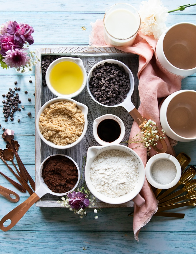 Ingredients in a tray for the brownie in a mug recipe including, cocoa powder, flour, brown sugar, oil, chocolate chips. vanilla, milk and oil