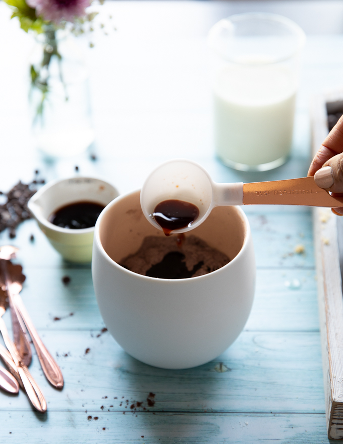 A hand adding the vanilla to the mug