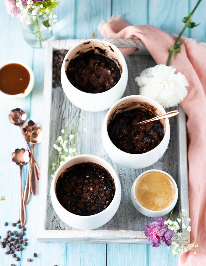 three mugs with brownies cooked in them on a tray with a cup of espresso on the side
