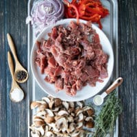A tray with thinly sliced meat, thinly sliced onion, peppers ad mushrooms. There are spoons of wslices on the side such as spoon of salt, spoon of pepper and spoon of onion powder and fresh herbs
