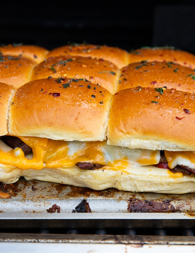 Philly cheesesteak sliders on the grill showing close up of the cheese melting and the sliders ready to eat