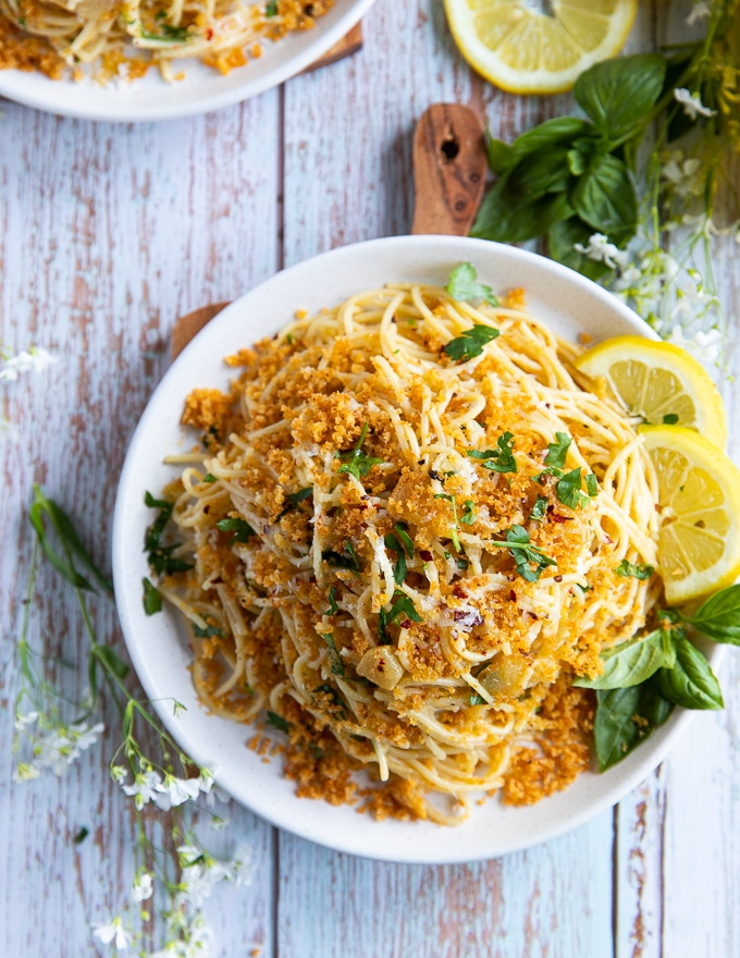 A single plate of spaghetti aglio e olio with lemon slices on the side and some fresh basil leaves