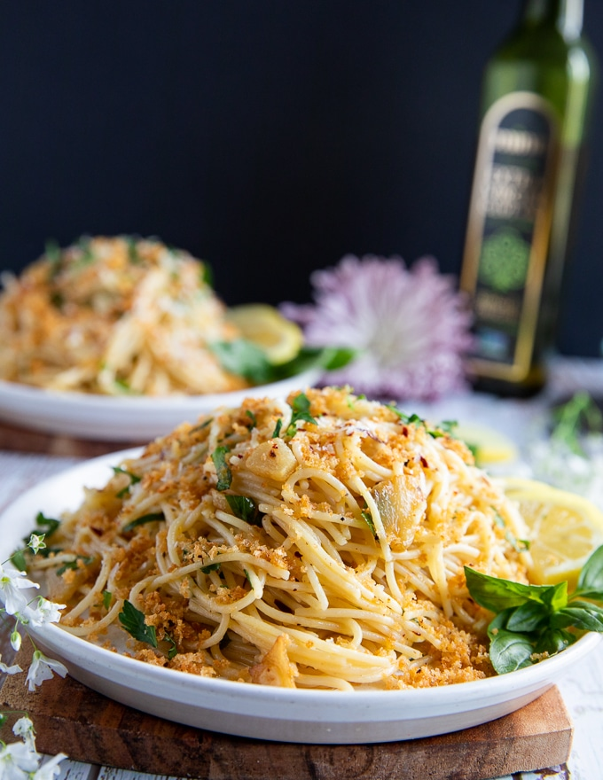 close up of the spaghetti aglio e olio dish showing the crunchy bread crumbs and fresh basil with sliced cooked garlic and olive oil
