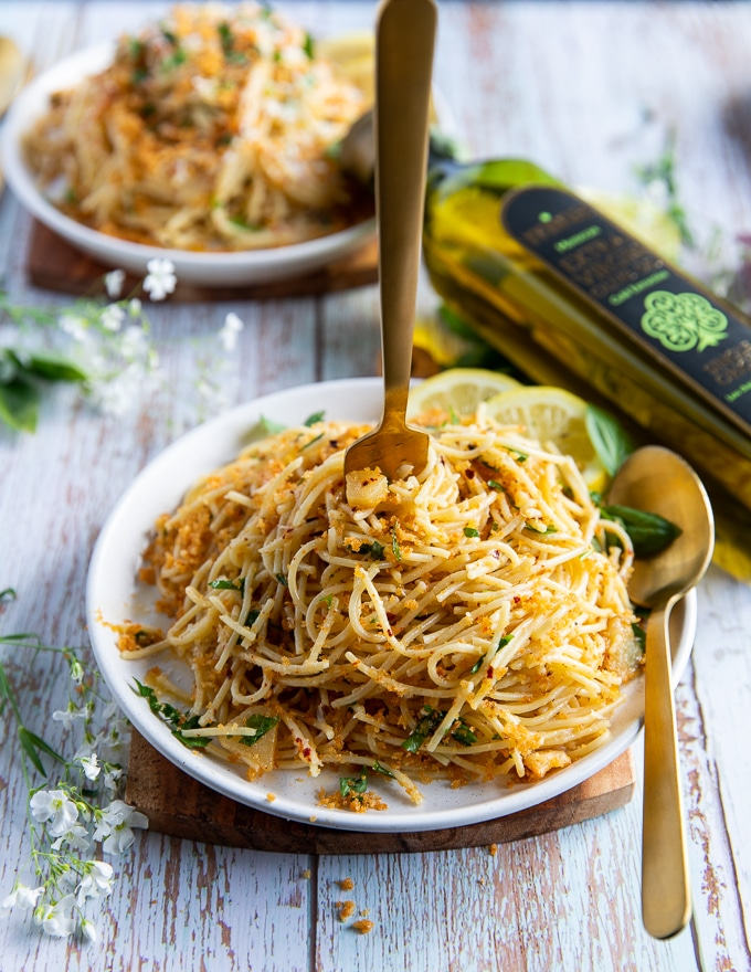 a hand eating some olive oil pasta with a fork and spoon swirling the spaghetti aglio e olio around showing the garlic, olive oil, basil and read crumbs