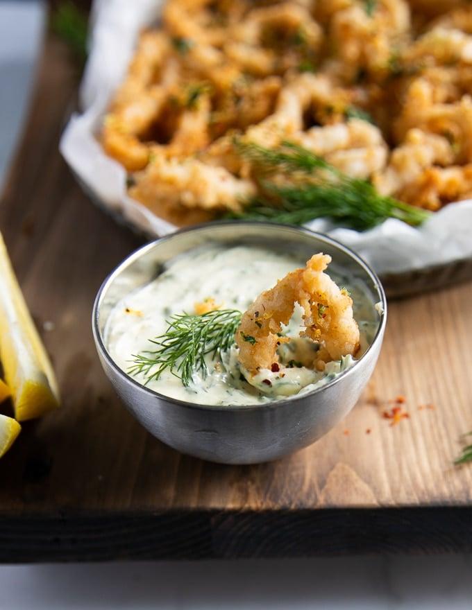 calamari dipped in tartar sauce, close-up view.
