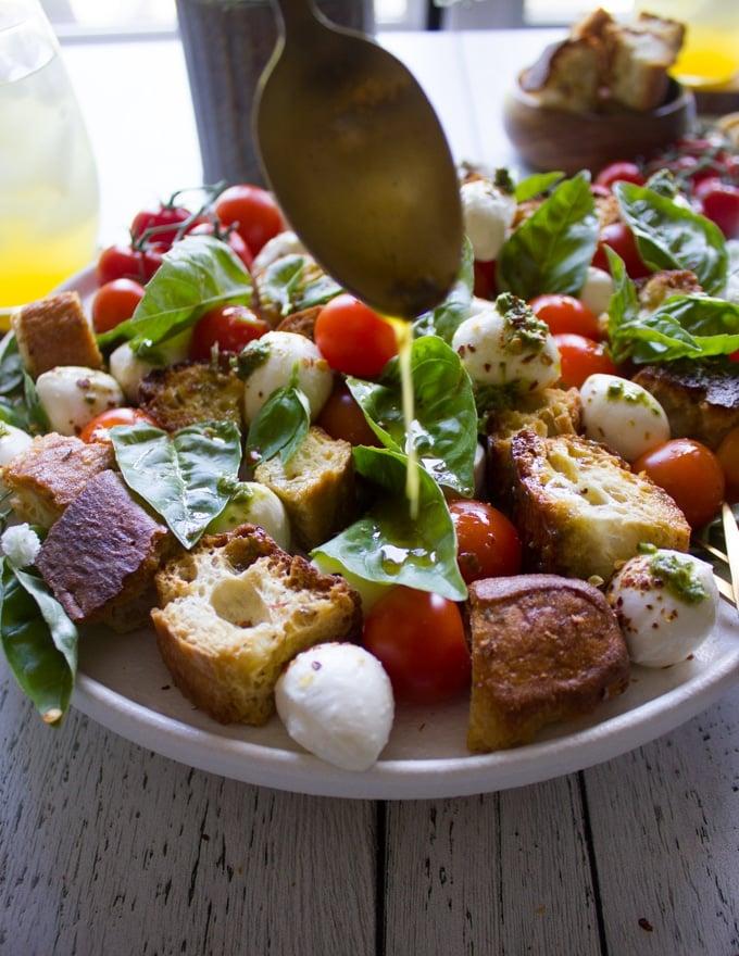 A spoon drizzling the delicious caprese salad dressing over caprese salad recipe