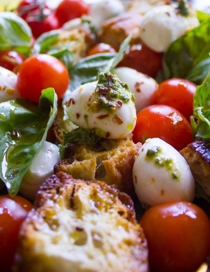 close up of one mozzarella and tomato bite of the caprese salad all dressed up with basil and some extra chilli flakes