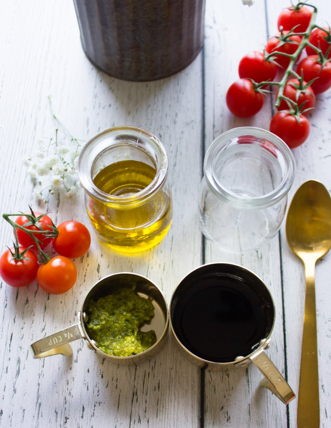 ingredients to make the caprese salad dressing including basil pesto, balsamic vinegar and olive oil