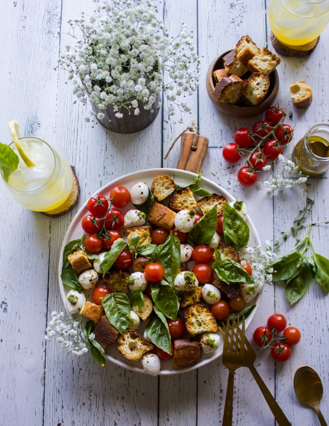 The caprese salad ready on a plate with extra croutons on the side and extra salad dressing.