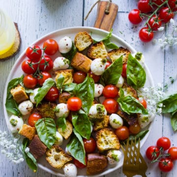A plate of caprese salad with basil leaves surrounding it and homemade croutons on a white board with cherry tomatoes around it