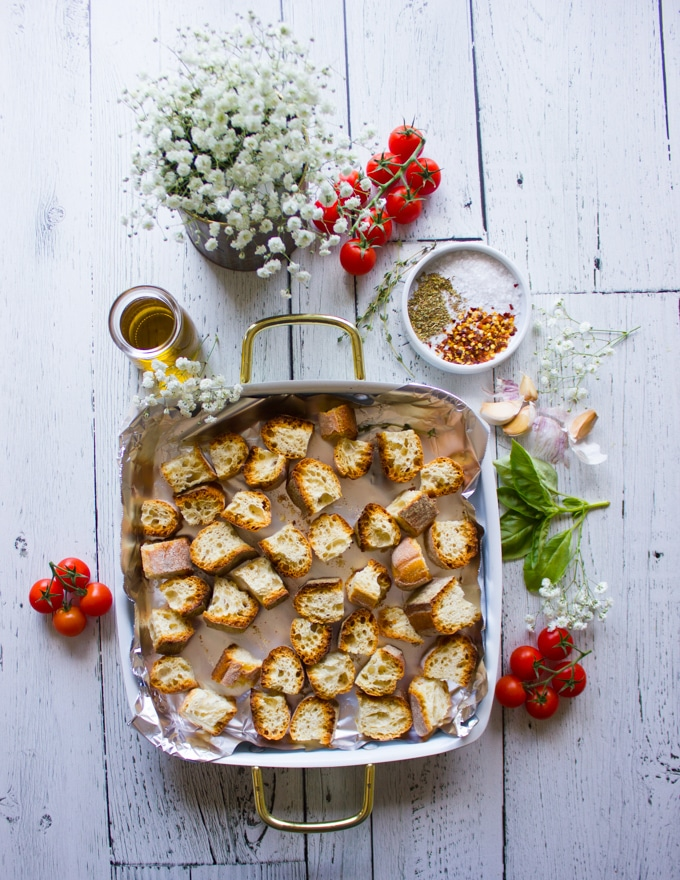 some stale bread chunks on an oven dish surrounded by garlic, olive oil, oregano and chilli flakes to make homemade croutons