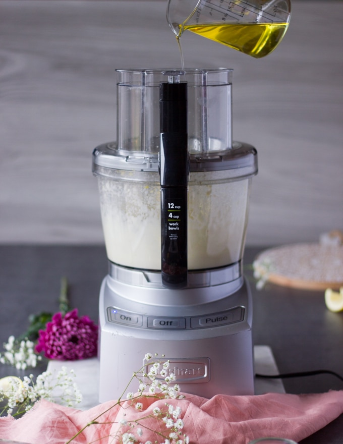 A hand drizzling oil in a thin stream through the feed of a food processor to make toum recipe