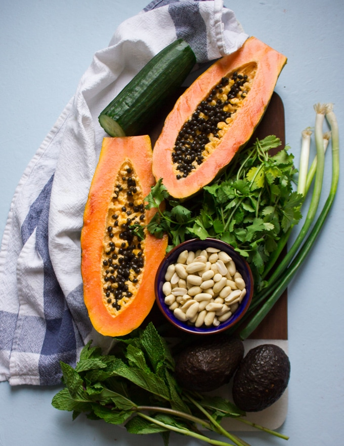 A papaya cut in half over a wooden board showing the beauty of this fruit surrounded by a bunch of cilantro, scallions and a cucumber