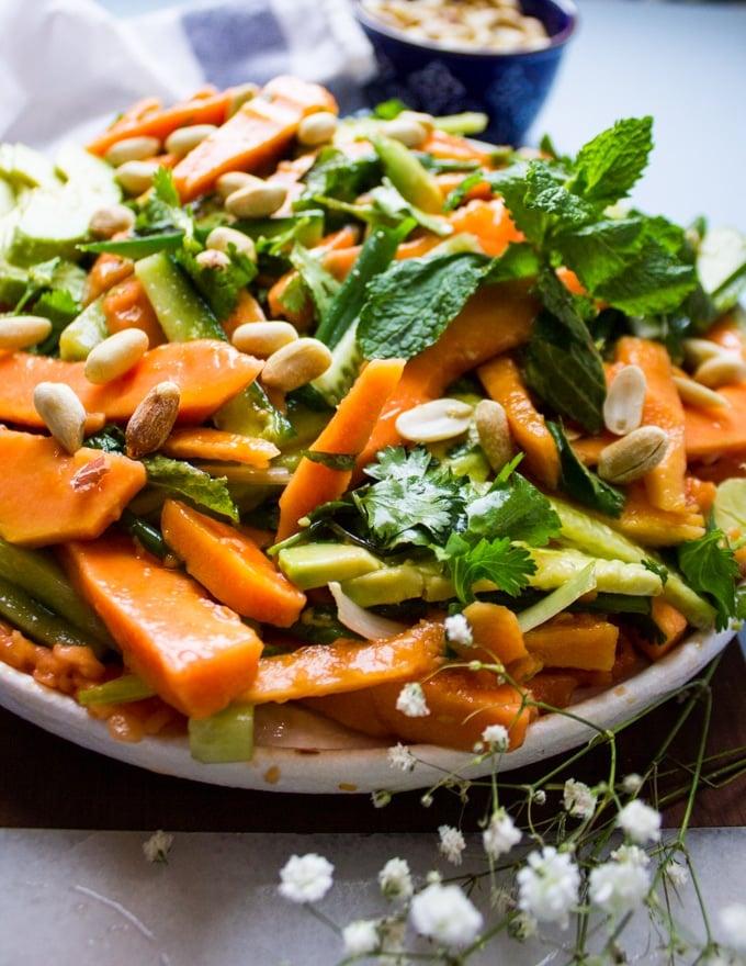 close up of the papaya salad on a plate showing the shredded papaya, cucumebrs, mint and cashews close up