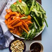papaya salad recipe ingredients in a bowl including papaya, avocados, cucumbers, scallions, fresh mint, cilantro, a bowl with papaya salad dressing and a bowl of cashews