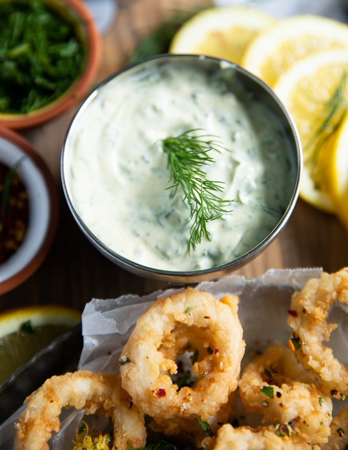 A bowl with tartar sauce and with a fresh dill sprig served close to a plate of calamari