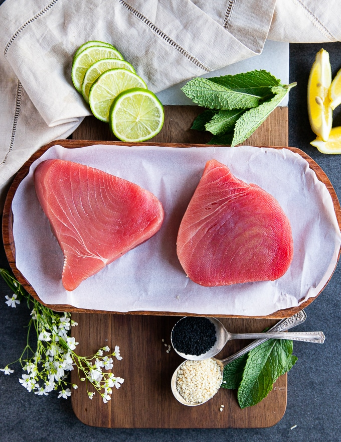 two tuna steaks on a parchment paper showing the fresh ahi tuna