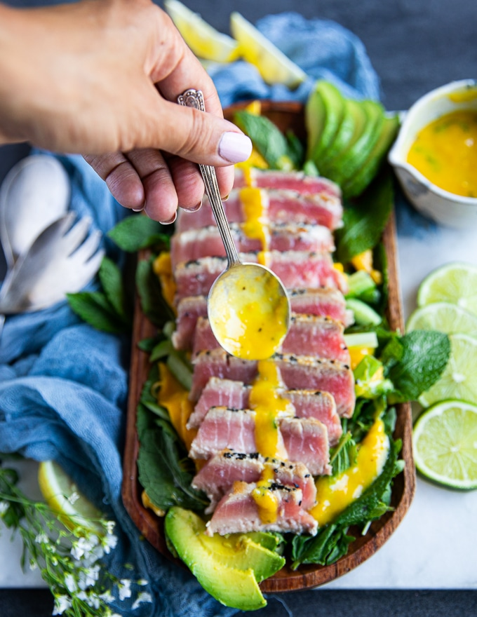 A hand holding a spoon full of mango dressing and drizzling it over the tuna steak recipe
